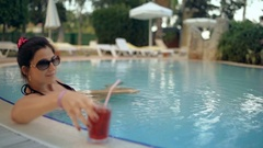 Beautiful lady drinking a cocktail in a swimming pool and relaxing. Stock Footage
