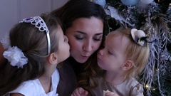 Happy family, two kids kissing mom near the christmas tree Stock Footage