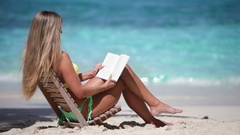 Woman sitting in teak chair reading on perfect tropical beach Stock Footage