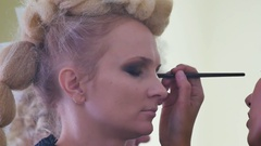 Make-up artist doing make-up powder causes a large brush close-up shot Stock Footage