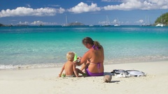 Mother putting snorkel gear on child at a tropical beach Stock Footage