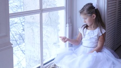 Sad child looking the window, snowing landscape Stock Footage