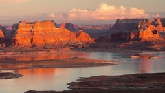Time lapse of cliffs lit up at sunset over lake in the Utah desert Stock Footage