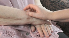 Woman holding flabby wrinkled hands of aged woman Stock Footage