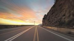 POV vehicle drive coast car travel road colorful sky sunset horizon rocky Stock Footage