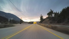 POV vehicle driving, remote countryside road tunnel passing car travel evening Stock Footage
