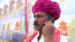 Handheld close up of a man talking serious on his cell phone in Rajasthan Stock Footage