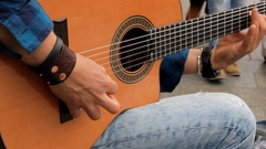 A man plays the guitar to passers people in the town square at the city festival Stock Footage
