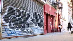 Pedestrians Walk Past Colorful Graffiti in Manhattan New York Stock Footage
