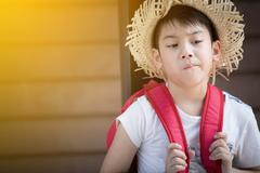 Asian bored child with red backpack is thinking while with sunl ight Stock Photos