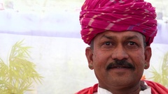 Portrait of a man with a red turban with a colourful tent backdrop Stock Footage