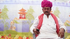 MS of Indian man seated and talking on the phone with traditional clothes Stock Footage