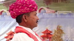 Hand-held side profile with a red turban with a colourful tent backdrop Stock Footage