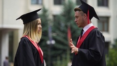 Two young people in mantles communicating before graduation ceremony outdoors Stock Footage