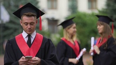 Man in academic dress and cap browsing on phone, women chatting on background Stock Footage