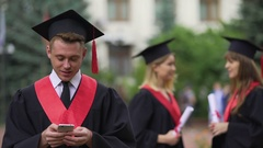 Male graduate reading good news on smartphone before ceremony, astonishment Stock Footage