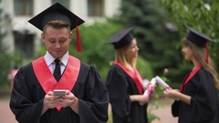 Graduate checking job offers on smartphone, reading messages in social network Stock Footage