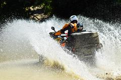The man on the ATV crosses a stream Stock Photos