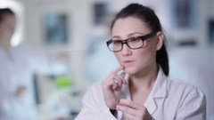 4K Scientist holding piece of clear material & using as interactive touch screen Stock Footage