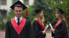 Graduation ceremony, happy man in academic dress looking into camera, laughing Stock Footage
