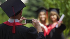 Two graduate girls holding diplomas and posing for smartphone camera, graduation Stock Footage
