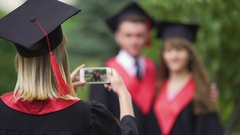 Female in academic dress and hat filming best friends on phone, graduation day Stock Footage