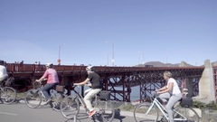 Panning past old women bicycling by Golden Gate Bridge - elderly ladies Stock Footage