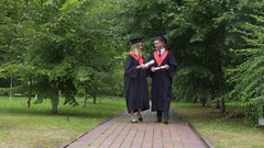 Young happy graduates holding diplomas and walking in park, talking and relaxing Stock Footage