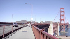 On pedestrian walkway at Golden Gate Bridge, panning from road to tower Stock Footage