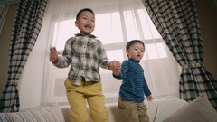 Two little boy of Asian appearance, having fun on the sofa in the room, jump and Stock Footage