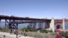 Panning across tourists taking picture with Golden Gate Bridge and water Stock Footage