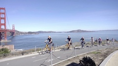 Bicyclists riding past Golden Gate Bridge on bicycles on clear day Stock Footage