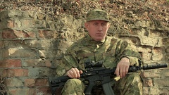 Soldier with automatic rifle sits near  brick wall  Stock Footage