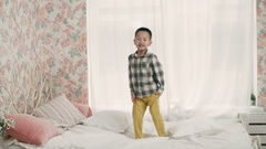 The little boy of Asian appearance, having fun on the bed in the room, laughing Stock Footage