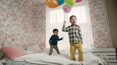 Two little boy of Asian appearance, having fun on the bed in the room, jump and Stock Footage