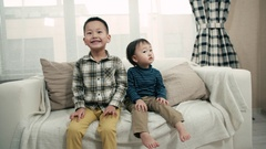 Two little boy of Asian appearance, having fun on the sofa in the room, make Stock Footage