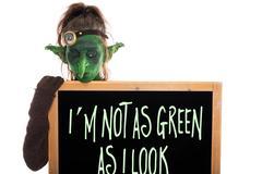 Green goblin with slate, englisch phrase, im not as green as i look Stock Photos