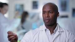 4K Portrait smiling scientist holding clear material & using as touch screen Stock Footage