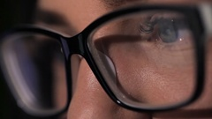 Attractive young woman using tablet touchscreen. Reflection of tablet in glasses Stock Footage