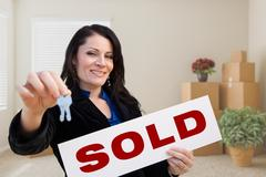 Hispanic Female Real Estate Agent with Sold Sign and Keys in Room with Moving Bo Stock Photos