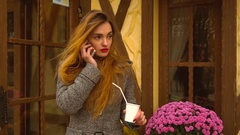 Redheaded girl drink coffee on the street Stock Footage