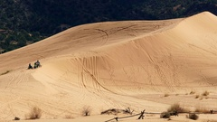 Person riding motorcycle through sand dunes and jumping a hill Stock Footage