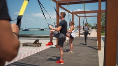 Outdoor TRX workout by the sea slow motion Stock Footage