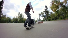 Skateboarder doing trick on grindbox in the skate park Stock Footage