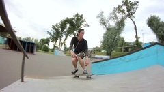 Young man doing a trick on a skateboard in a skate park Stock Footage