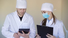 Serious looking doctors consulting something over tablet computer Stock Footage