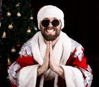 Bad rastoman Santa Claus smiles and making hands sign namaste on the background Stock Photos
