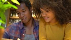 Cheerful couple in restaurant choosing menu Stock Footage