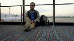 Man waiting for flight at airport sitting on the floor. Airplane delay Stock Footage