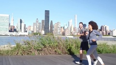 Couple running on Long Island, along East river Stock Footage